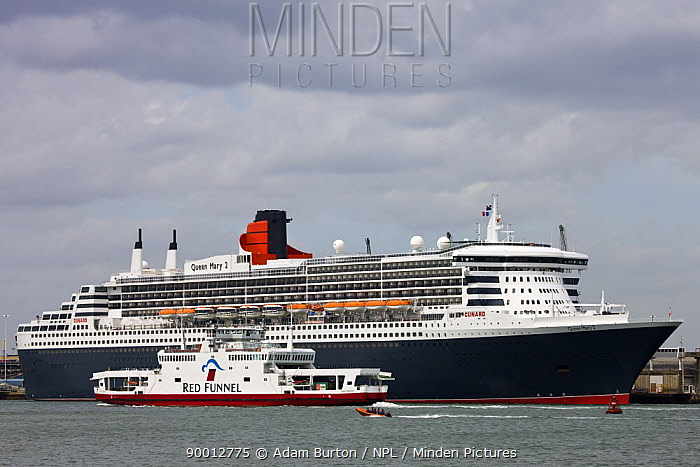 Isle of Wight ferry passes Cunard liner Queen Mary 2 in Southampton Water, Hampshire, England  -  Adam Burton/ npl