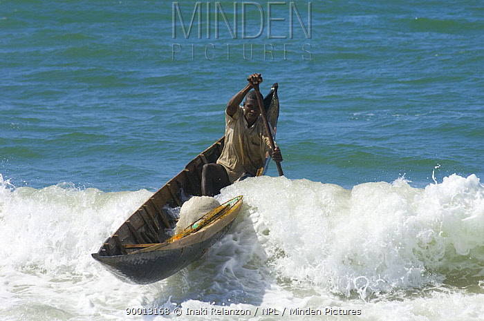 Fisherman in boat paddling through the surf, Antaimoro tribe, Channel des Pangalanes, Madagascar  -  Inaki Relanzon/ npl