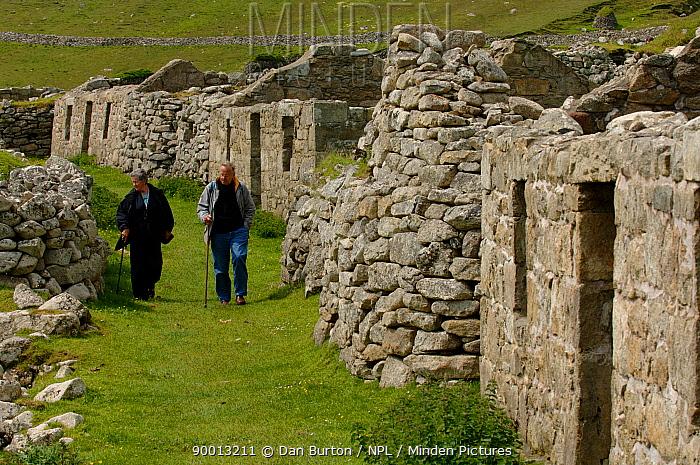People walking past abandoned stone brick houses, Hirta, Saint, St Kilda Island, Western Islands, Outer Hebrides, Scotland  -  Dan Burton/ npl