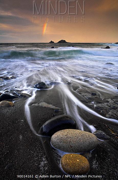 Pebbles on beach at sunrise, with the Brisons rocks and a rainbow, Cape Cornwall, UK  -  Adam Burton/ npl