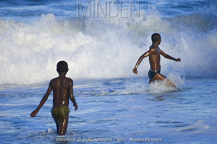 Two boys playing in the surf on the beach, Manakara town, East Coast of Madagascar  -  Inaki Relanzon/ npl