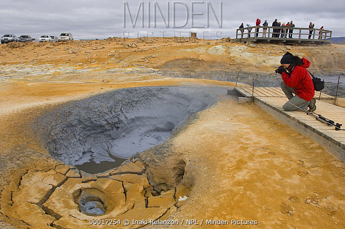 Person photographing bubbling hot mud springs, geothermal area of Krafla, North Iceland  -  Inaki Relanzon/ npl