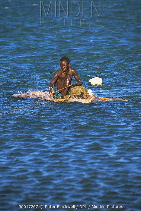 Fisherman on raft boat pulling in his net, Lake Turkana, Kenya, 2006  -  Peter Blackwell/ npl