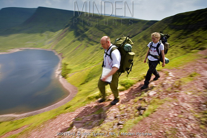 Walkers carrying backpacks hiking above Llyn y Fan Fach, a glacial cirque, beneath Black Mountain in the Brecon Beacons National Park, Powys, Wales  -  Nick Turner/ npl