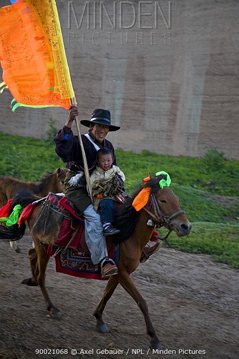 Man and boy riding horse to holy mountain, Dargye, Sichuan, Tibet, China  -  Dr. Axel Gebauer/ npl