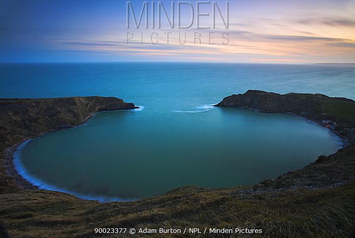 Twilight on clifftops overlooking the circular Lulworth Cove, Dorset, England Jurassic Coast World Heritage Site  -  Adam Burton/ npl
