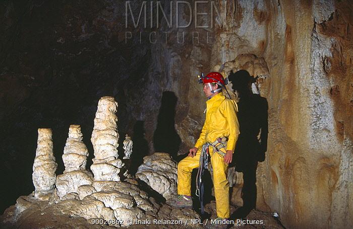 Potholer in underground cave system beside stalagmites, Graller del Boixaguer, Serra del Montsec, Lleida, Spain, October 1994  -  Inaki Relanzon/ npl