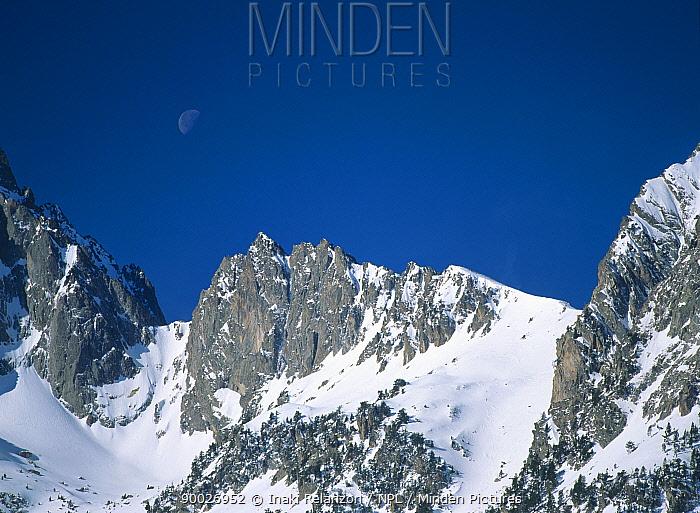 Moon above snow-covered rocky peaks in d'Aiguestortes National Park, Pallars Sobira, Catalonia, Spanish Pyrenees  -  Inaki Relanzon/ npl