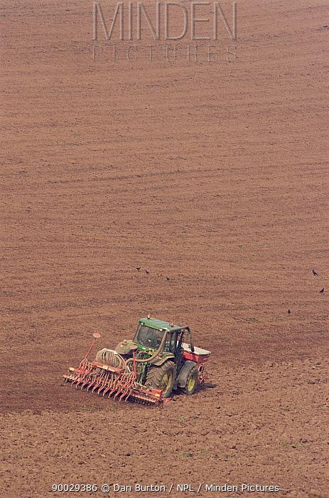 Tractor raking field and treating with chemicals, Devon, UK  -  Dan Burton/ npl
