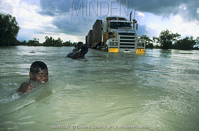 Aborigine children playing in flooded river beside stranded vehicle, Queensland, Australia  -  Laurent Geslin/ npl
