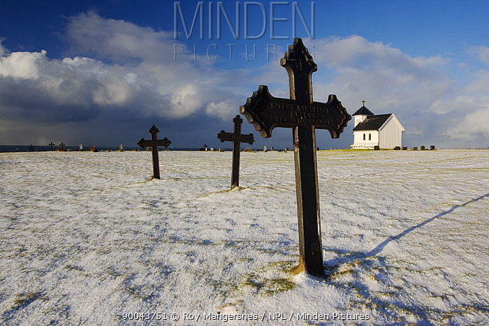 Snow covers the ground of the old churchyard of Varhaug, H?, Rogaland, Norway Note World War II bullet hole in Iron cross February  -  Roy Mangersnes/ npl