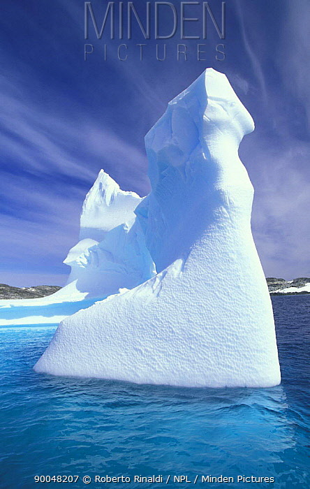 Carved iceberg with cloud formations in the background, Antarctic Peninsula  -  Roberto Rinaldi/ npl
