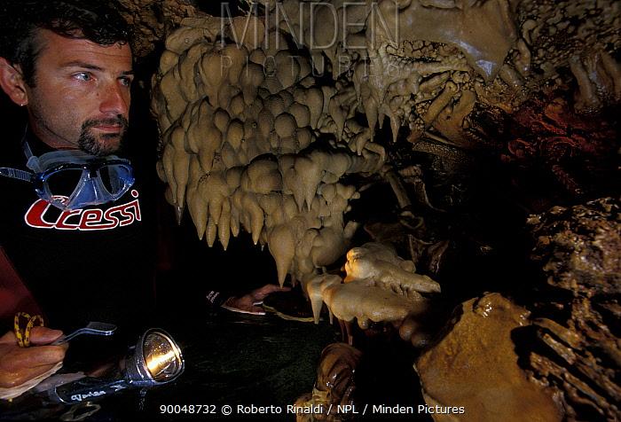 Diver in Deer Cave (grotta dei cervi), Alghero, Sardinia, Italy, looking at stalactites  -  Roberto Rinaldi/ npl
