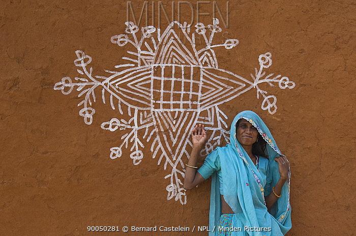 Rajasthani woman standing beside traditional painting on mud wall of house during Diwali festival, south of Bundi, Rajasthan India  -  Bernard Castelein/ npl