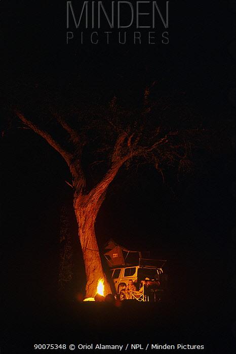 Travellers beside campfire at night, Savuti, Chobe National Park, Botswana, October  -  Oriol Alamany/ npl