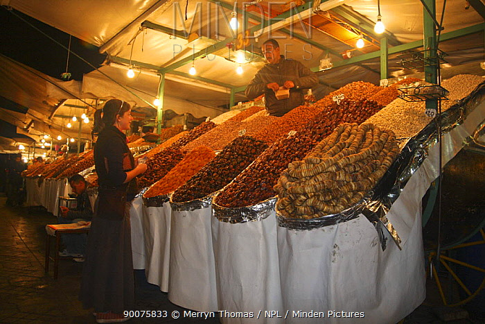 Woman buying dried fruit from night souk, Djemaa el-Fna town square, Marrakech, Morocco November 2008  -  Merryn Thomas/ npl
