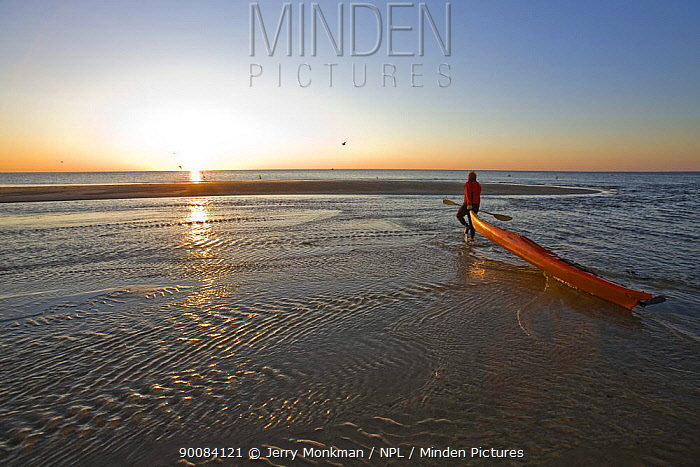 A man taking sea kayak at dawn to sea at the Shifting Lots Preserve in Plymouth, Massachusetts, USA Owned by the Wildlands Trust Cape Cod Bay Near Ellisville Harbor State Park Model Released May 2008  -  Jerry Monkman/ npl