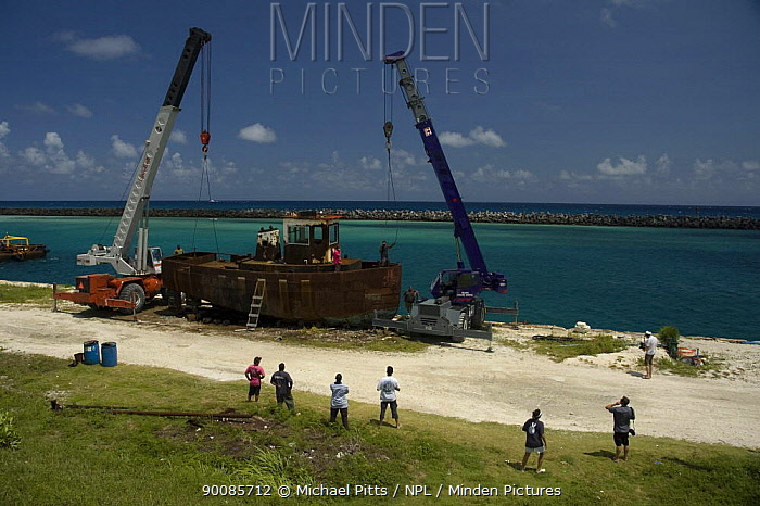 Cranes being rigged to the hulk of tugboat ''Blue Plunder'' prior to towing out to sea and sinking Nassau, Bahamas August 2007  -  Michael Pitts/ npl
