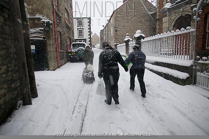 People carrying shopping along snow covered street, Denbigh, Denbighshire, Wales, January 2010  -  David Woodfall/ npl