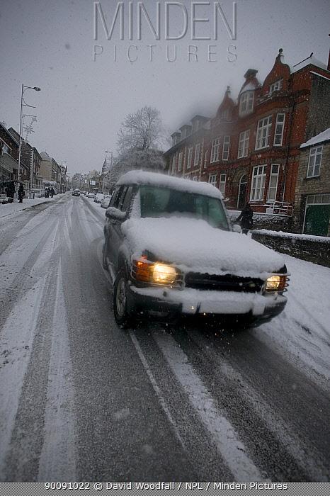 Cars driving along snow covered road, Denbigh, Denbighshire, Wales, January 2010  -  David Woodfall/ npl