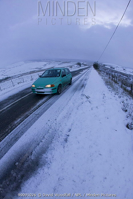 Car driving along moorland road in bad snow conditions, Denbigh Moor, Denbighshire, Wales, December 2009  -  David Woodfall/ npl