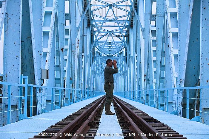 Nature manager and controller Bojan T on railway bridge, the border between Croatia and Serbia, looking with binoculars, Gornje Podunavlje Special Nature Reserve, Serbia, June 2009  -  WWE/ Smit/ npl
