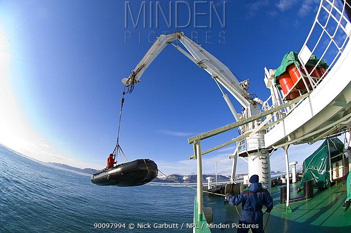 Lifting tourist Zodiac inflatable boat onto mother ship, Akademik Ioffe, Spitsbergen, Svalbard, Arctic Norway, June 2009  -  Nick Garbutt/ npl