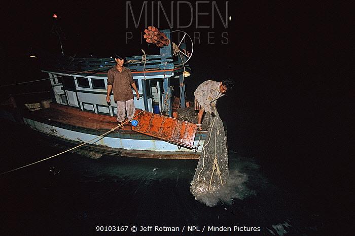 Hauling in net on fishing dragger at night, Sihanoukville, Cambodia, Kampuchea, June 2008  -  Jeff Rotman/ npl