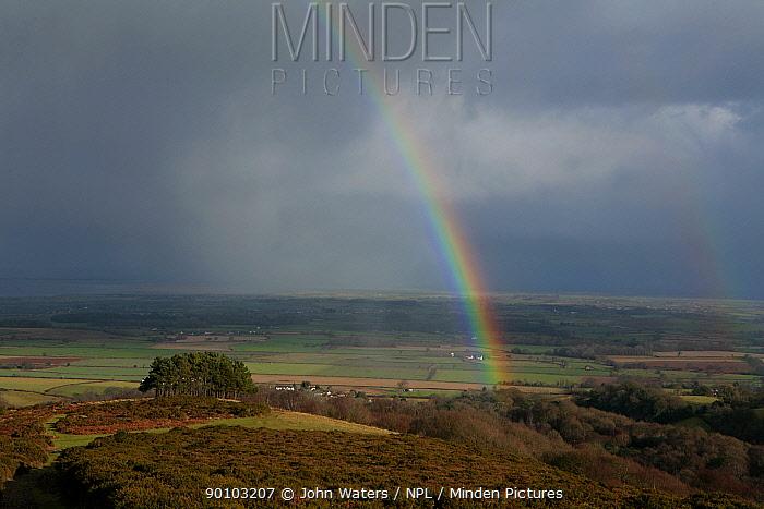 Looking north from summit ridge of Quantocks range of hills, towards Somerset Levels with rain shower and rainbow, Somerset, UK  -  John Waters/ npl