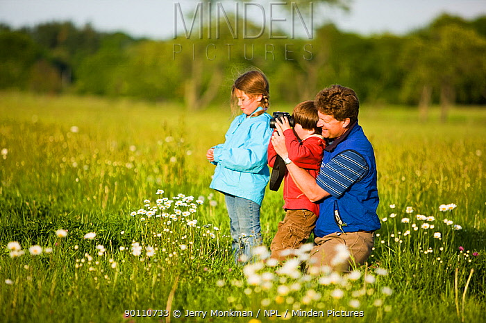 Father and his two children birdwatching in a hay field on a farm in Ipswich, Massachusetts, USA, May 2009 Model released  -  Jerry Monkman/ npl