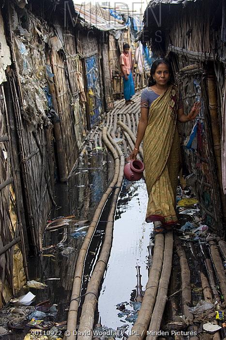 Woman walking through polluted slum, Dhaka, Bangladesh, July 2008  -  David Woodfall/ npl