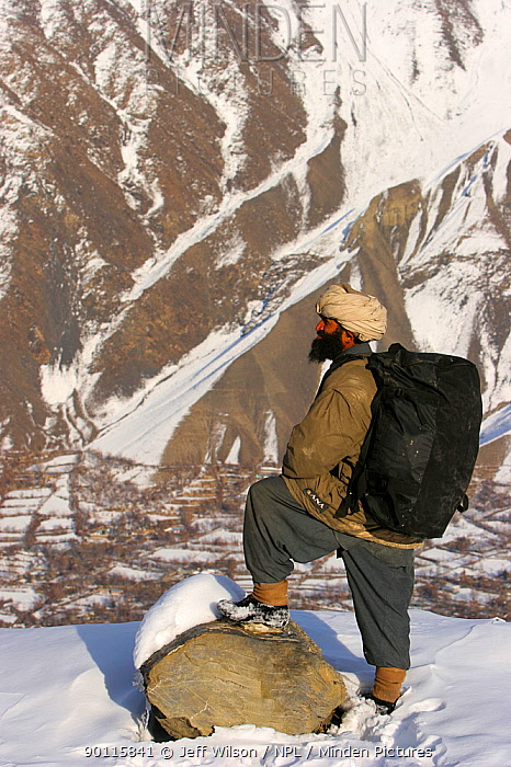 Porter carrying film crew equipment, above Chitral town in the Hindu Kush mountains, North West Frontier, Pakistan, during filming for BBC Planet Earth series, Mountains episode, 2005  -  Jeff Wilson/ npl