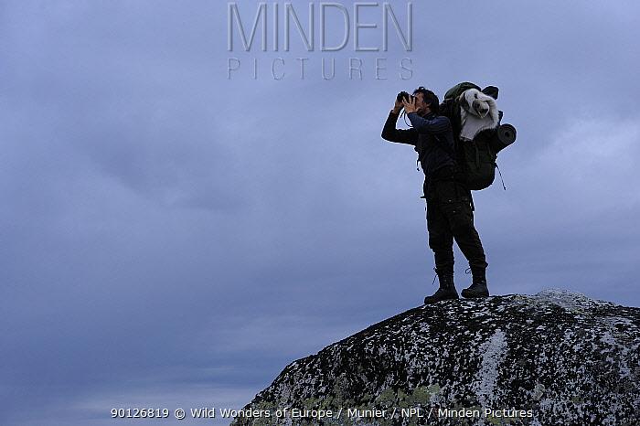 Photographer, Vincent Munier, standing on large rock looking through binoculars, Forollhogna National Park, Norway, September 2008  -  WWE/ Munier/ npl