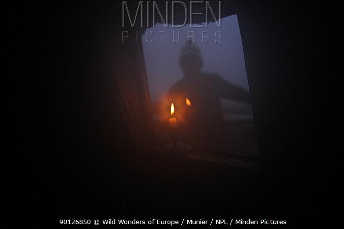 Photographer, Vincent Munier, looking through window, silhoutted at night, Forollhogna National Park, Norway, September 2008  -  WWE/ Munier/ npl