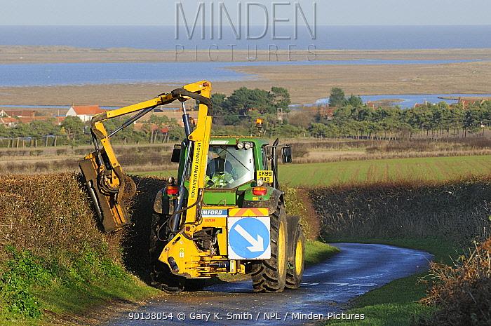 Mechanised hedge cutting on minor coastal road, with coastline in distance Norfolk, UK, December 2009  -  Gary K. Smith/ npl