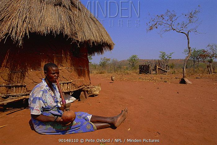 Tonga woman smoking marijuana outside village hut, Lake Kariba, Zimbabwe  -  Pete Oxford/ npl