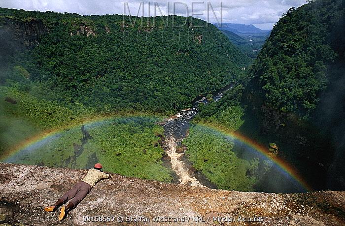 Man overlooking Kaieteur Falls Gorge with rainbow, Guyana, South America  -  Staffan Widstrand/ npl