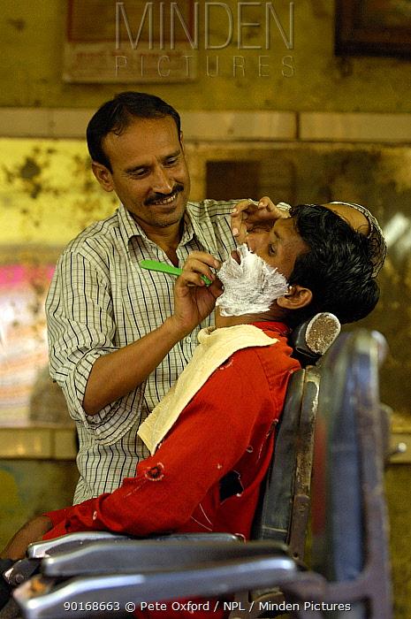 Barber shaving man in Barber shop, Bharatpur village, Rajasthan, India 2006  -  Pete Oxford/ npl