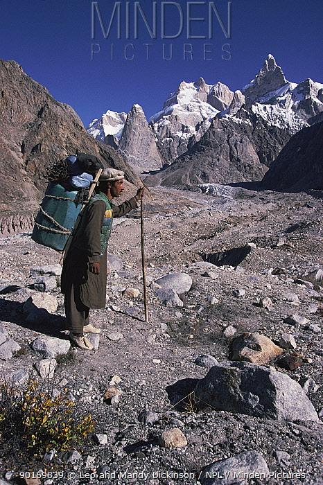 Porter carrying load on moraine, Karakorum, Pakistan  -  Leo & Mandy Dickinson/ npl