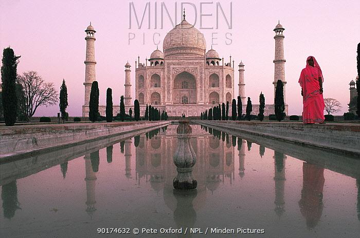 Famous landmark, the Taj Mahal with Indian woman in traditional sari, at sunrise, Agra, Uttar Pradesh, India  -  Pete Oxford/ npl