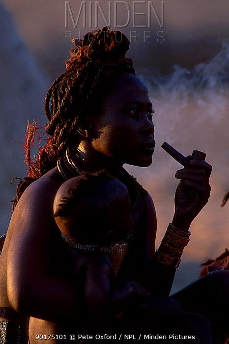 Himba woman in traditional dress smoking pipe Kaokoland Namibia  -  Pete Oxford/ npl