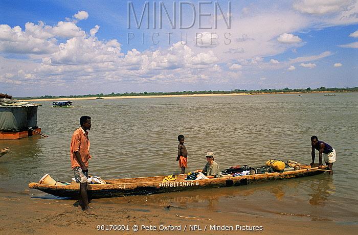Tourist in dugout canoe crossing Tsiribihina river, Western Madagascar  -  Pete Oxford/ npl