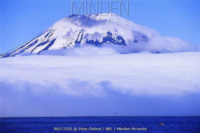 Amukta Island with volcano looming above clouds, with Northern fulmars in flight below, Aleutian Islands, Alaska, USA  -  Pete Oxford/ npl