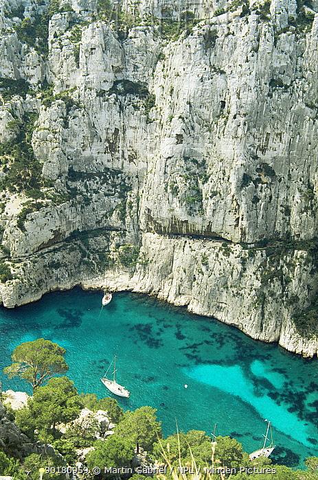 Boats on sea at foot of limestone cliffs, Calanques, Southern France  -  Martin Gabriel/ npl