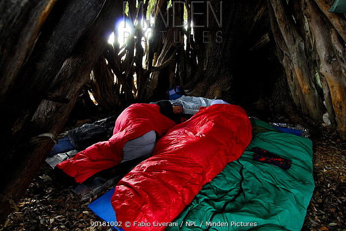 People in sleeping bags resting during day, in traditional sardinian goat hut, Sardinia, Italy  -  Fabio Liverani/ npl