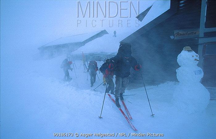 Hikers putting on skiis outside mountain hut in snow storm Finse, Hardangervidda, Norway  -  Asgeir Helgestad/ npl
