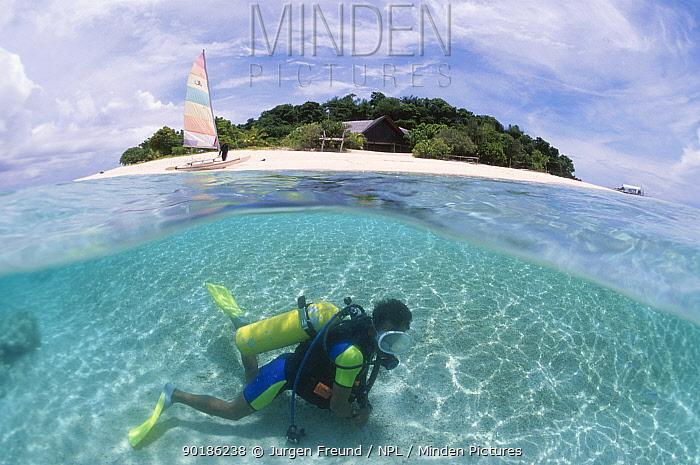 Diver in shallow water split level Philippines  -  Jurgen Freund/ npl