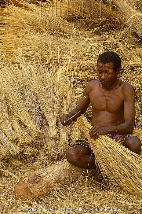 Sakalva man preparing thatch grass, wearing an amulet or 'ody fitahantena' to protect him from bad spirits Ankarafantsika Nature Reserve, MADAGASCAR 2005  -  Pete Oxford/ npl