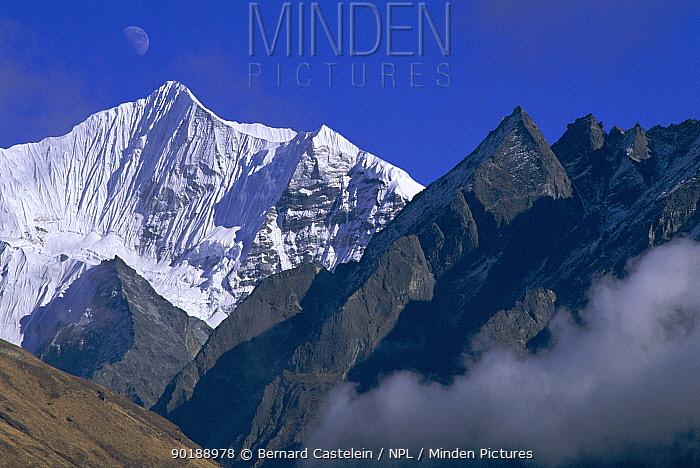 Langshisa-ri seen from Kyanjing Gompa (3500metres) with moon in sky, Langtang NP, Nepal  -  Bernard Castelein/ npl
