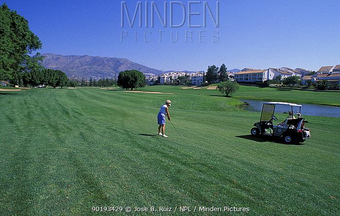 Golfer on golf course with golf buggy, Fuengirola, Malaga, Spain  -  Jose B. Ruiz/ npl